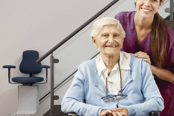 Senior and nurse in the house with stair lift as a nursing service concept